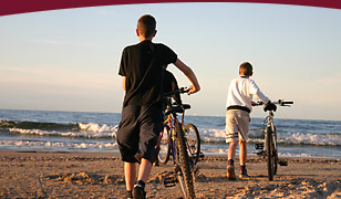 Image: Two young cyclists along Nova Scotia seashore